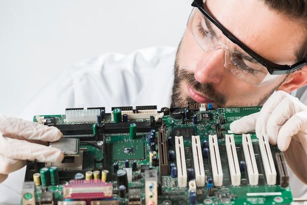 Nahaufnahme einer tragenden sicherheitsbrille des männlichen technikers, die chip in computermotherboard einfügt