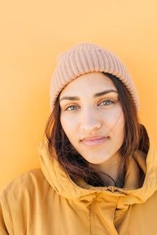 Nahaufnahme einer tragenden strickmütze der hübschen frau, die kamera betrachtet