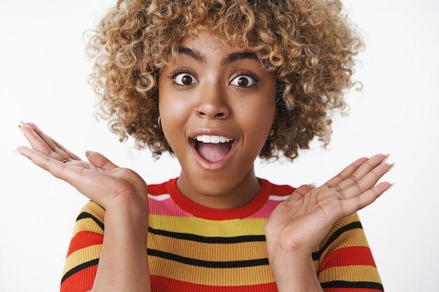 Nahaufnahme einer überraschten optimistischen und aufgeregten süßen afroamerikanerin gewann ein tolles geschenk, das tolle winterferien verbringen wird, erstaunt und glücklich offenen mund, lächelt und die hände seitlich ausbreitet