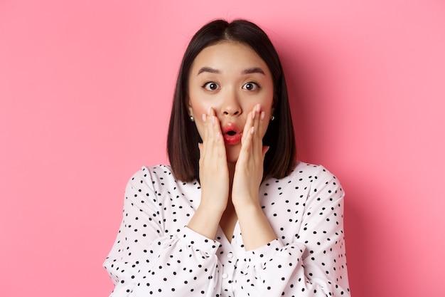 Nahaufnahme einer überraschten und erstaunten asiatischen frau, die in die kamera starrt und keucht beeindruckt, händchen haltend in der nähe...