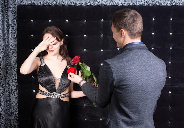 Nahaufnahme einer überwältigten jungen frau in einem eleganten schwarzen kleid, die von ihrem glücklichen freund eine rote rose und eine rote schmuckschatulle erhielt
