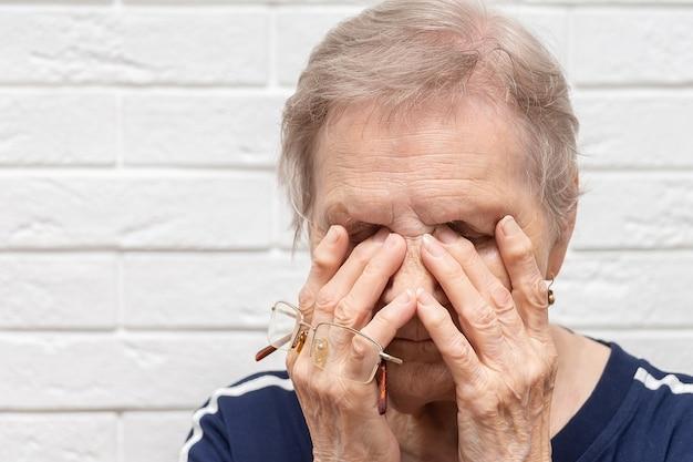 Nahaufnahme einer ungesunden älteren frau, die die brille abnimmt, die augen massieren, die an starker migräne oder kopfschmerzen leiden, unwohl kranke ältere weibliche großmutter kämpft mit verschwommenem sehen oder schwindel zu hause