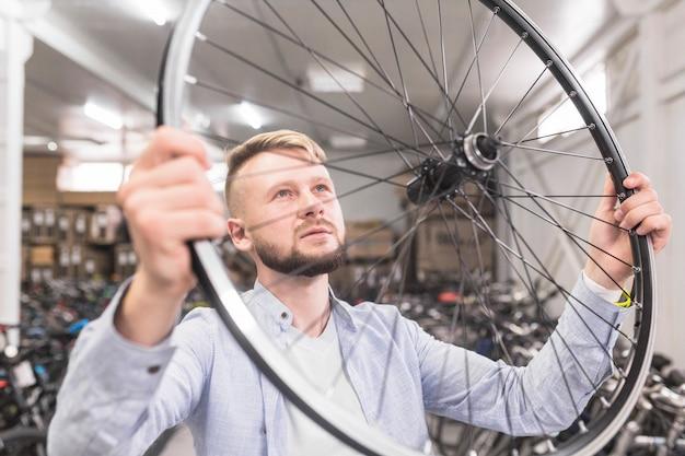 Nahaufnahme einer untersuchenden fahrradfelge des mannes im shop