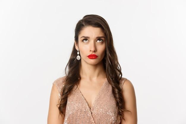 Nahaufnahme einer unzufriedenen jungen frau mit frisur und make-up, die auf die top-werbung blickt und auf weißem hintergrund steht