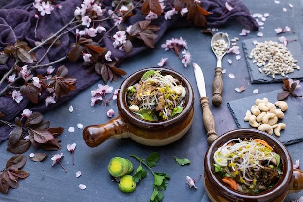 Nahaufnahme einer veganen mahlzeit mit pilzen, zwiebeln, karotten und lauch