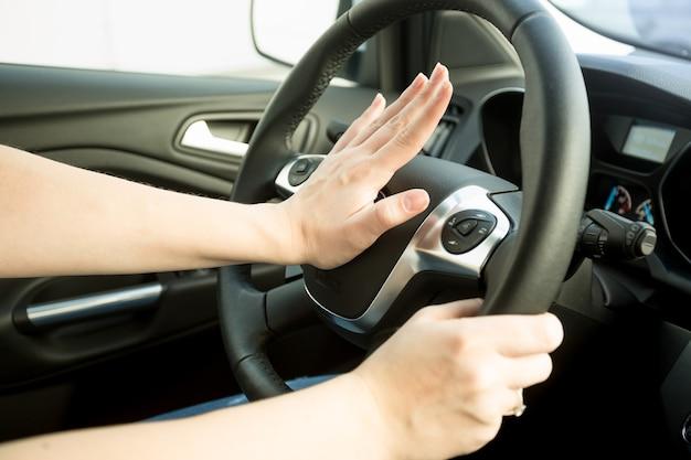 Nahaufnahme einer verärgerten frau, die auto fährt und hupt