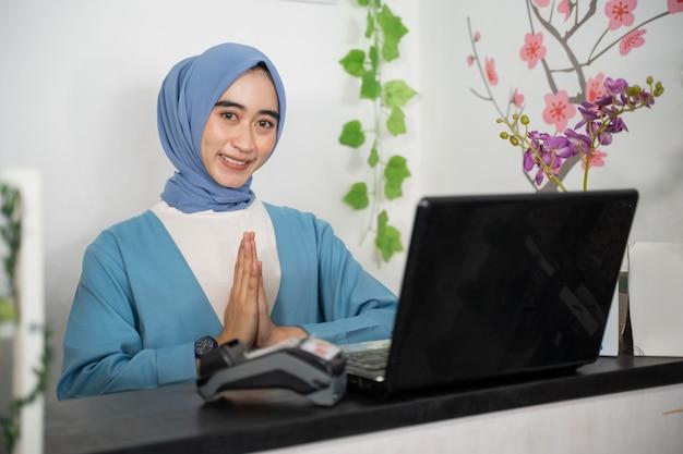 Nahaufnahme einer verschleierten geschäftsfrau, die mit einer grußgeste lächelt, während sie vor einem laptop sitzt...