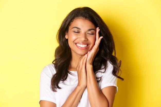 Nahaufnahme einer verträumten, schönen afroamerikanischen frau, die das gesicht sanft berührt und erfreut lächelt, vor gelbem hintergrund stehend