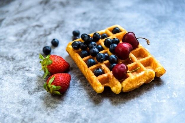 Nahaufnahme einer waffel mit blaubeeren und erdbeeren mit köstlichem aspekt