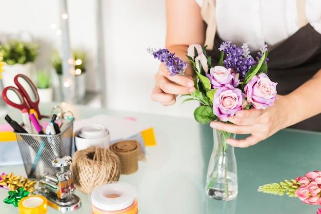 Nahaufnahme einer weiblichen floristenhand, die blumen im vase auf glasschreibtisch anordnet