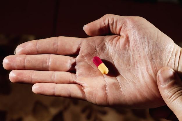 Nahaufnahme einer weiblichen hand, die eine weiße pille hält