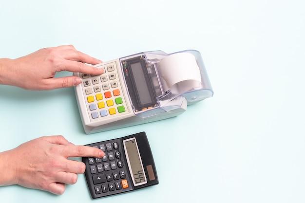 Nahaufnahme einer weiblichen hand, die einen finger in einem registrierkassenknopf drückt, und einer hand, die einen knopf in einem taschenrechner drückt