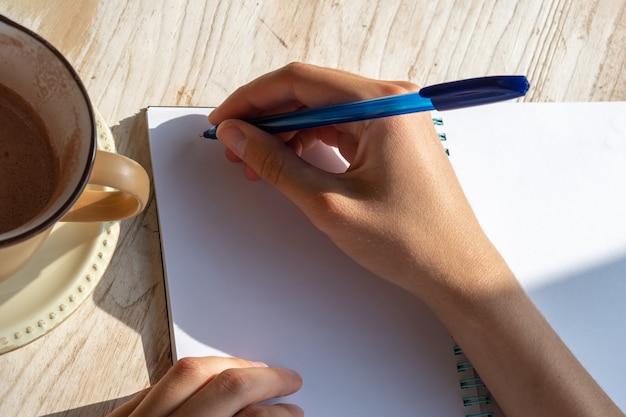 Nahaufnahme einer weiblichen hand, die text in einem kugelschreiber in einem leeren notizbuch mit einer tasse kaffee auf einem tisch in einem café aufschreibt. morgenplanung mit einer tasse kakao oder kaffee.