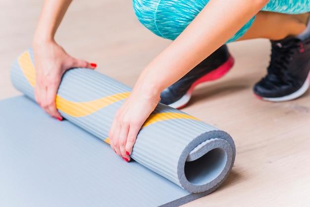 Nahaufnahme einer weiblichen hand faltenden yogamatte