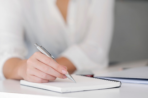 Nahaufnahme einer weiblichen handschrift etwas auf notizbuch auf dem vordergrund.