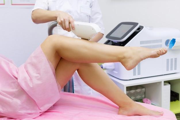 Nahaufnahme einer weiblichen kosmetikerin, die eine junge frau zu einem verfahren zur laser-haarentfernung für das bein macht