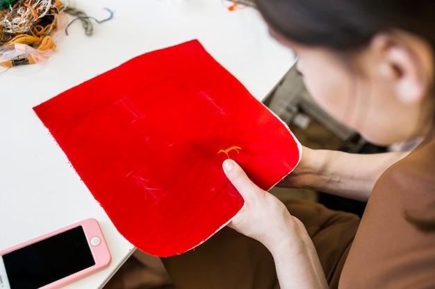 Nahaufnahme einer weiblichen näherin, die roten stoff mit nadel näht