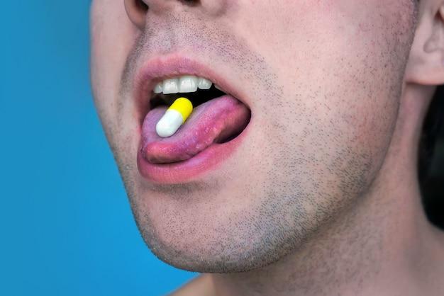 Nahaufnahme einer weißen pille im mund des mannes. runde tablette auf der zunge