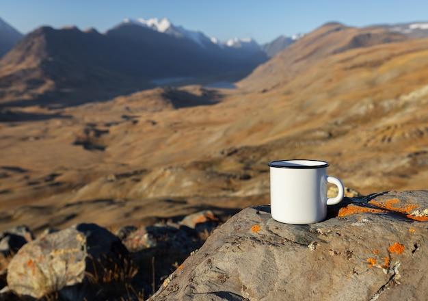 Nahaufnahme einer weißen tasse auf einem stein vor dem hintergrund einer bergkette