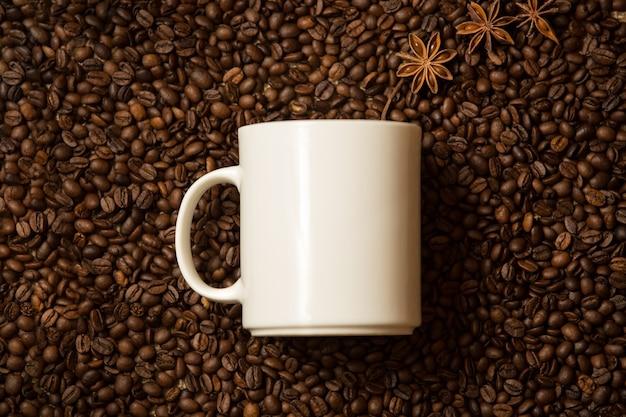 Nahaufnahme einer weißen tasse gegen kaffeebohnen mit anissternen, die wie dampf liegen lying
