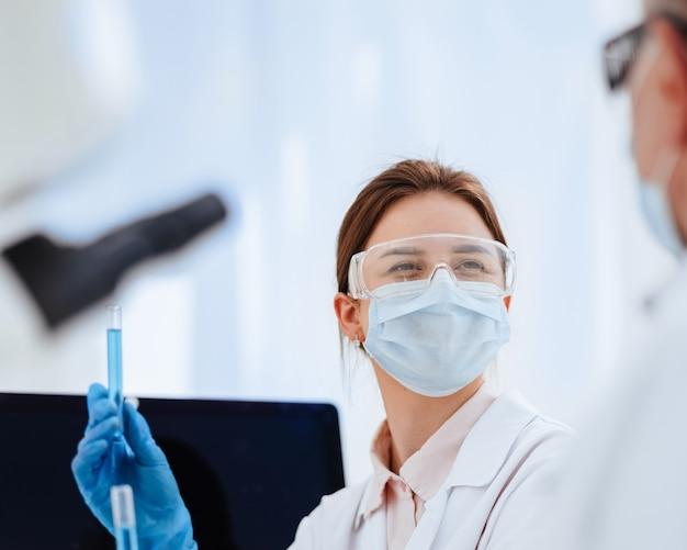 Nahaufnahme einer wissenschaftlerin, die flüssigkeit in reagenzgläsern betrachtet