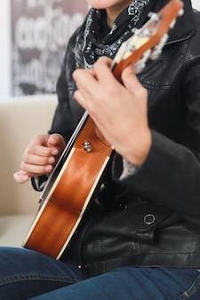 Nahaufnahme einer woma-hände, die die ukulele spielen hipster-frau, die gitarre spielt, die lernt, ukulele zu spielen?