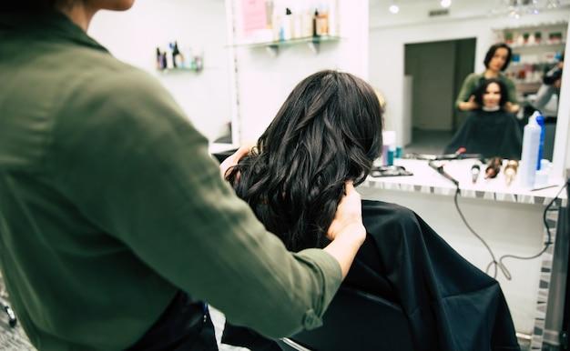 Nahaufnahme einer wunderschönen frau mit schönem, welligem haar, die sich in einem schönheitssalon die haare machen lässt.