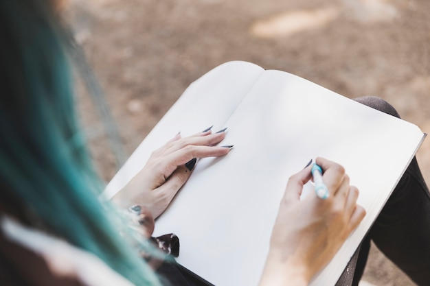 Nahaufnahme einer zeichnung der jungen frau auf einfachem notizbuch mit stift