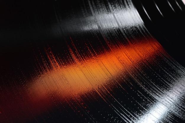 Nahaufnahme eines 12-zoll-lp-vinyl-schallplatten-grooves mit weißen und orangefarbenen lichtern.