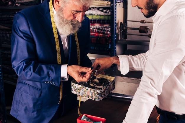 Nahaufnahme eines älteren männlichen schneiders mit messendem band um seinen hals, der seinem kunden knopf zeigt
