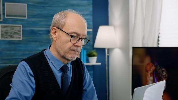 Nahaufnahme eines älteren mannes, der am laptop schreibt, der von zu hause aus arbeitet und das finanzprojekt analysiert. eleganter pensionierter angestellter mit brille mit moderner technologie zum lesen am computer