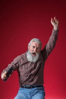 Nahaufnahme eines älteren mannes, der in der hand fernbedienung zujubelt gegen roten hintergrund hält