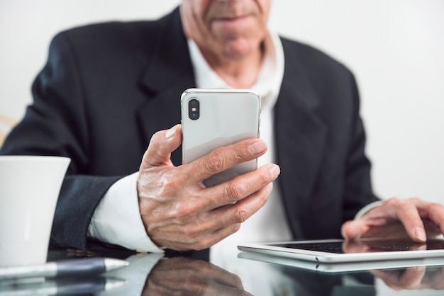 Nahaufnahme eines älteren mannes, der in der hand intelligentes telefon hält