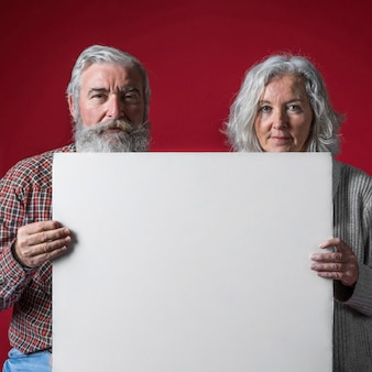 Nahaufnahme eines älteren paares, das leeres weißes plakat gegen farbigen hintergrund hält