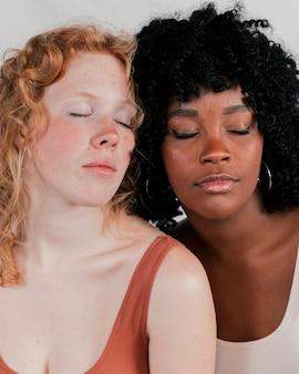 Nahaufnahme eines afrikaners und der blonden jungen frauen mit auge schloss
