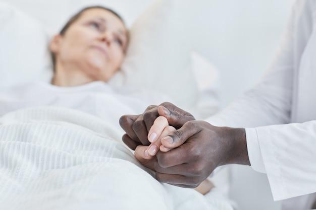 Nahaufnahme eines afrikanischen arztes, der seine patientin an der hand hält und sie im krankenhaus unterstützt