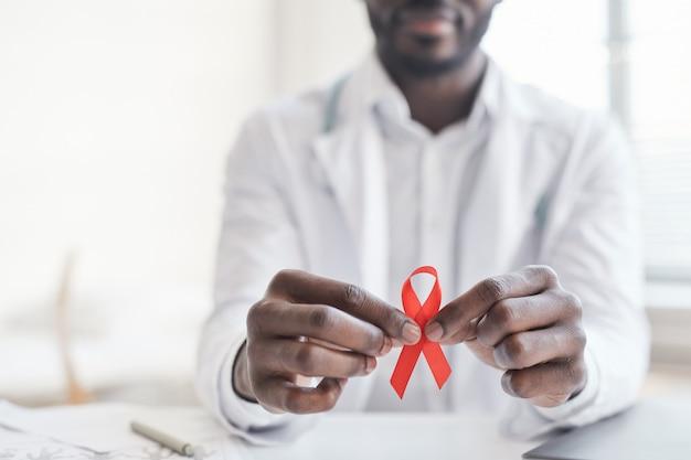 Nahaufnahme eines afrikanischen arztes mit rotem band in den händen im krankenhaus