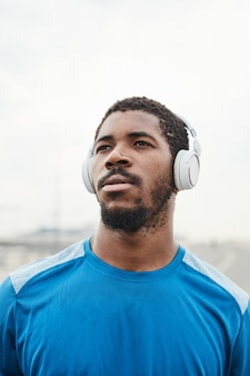 Nahaufnahme eines afrikanischen jungen mannes in drahtlosen kopfhörern, der beim training an der frischen luft wegschaut