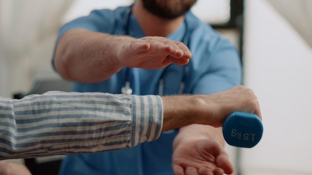 Nahaufnahme eines alten patienten, der hanteln für körperliche aktivität hält