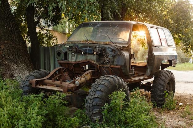 Nahaufnahme eines alten rostigen autos mit gebrochener tür und ohne räder auf eines grünen nadelwaldes