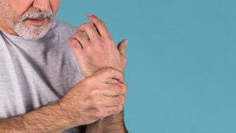 Nahaufnahme eines älteren Mannes, der ihr schmerzliches Handgelenk hält