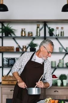 Nahaufnahme eines älteren Mannes, der Lebensmittel in der Küche kocht