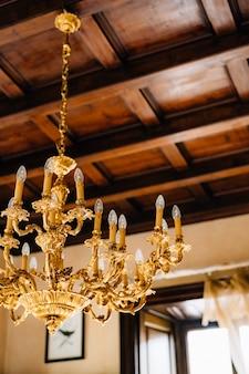 Nahaufnahme eines antiken goldenen kronleuchters im inneren einer alten villa