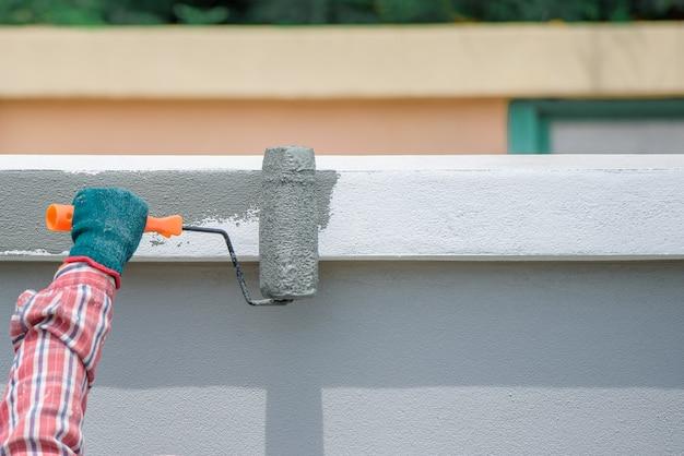 Nahaufnahme eines arbeiters, der die wände des hauses von hand und pinsel rollt. graue oder zementfarbene farbe
