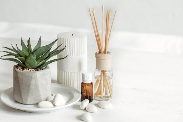 Nahaufnahme eines aromasticks für einen raumgeruch und ein glas aromaöl.