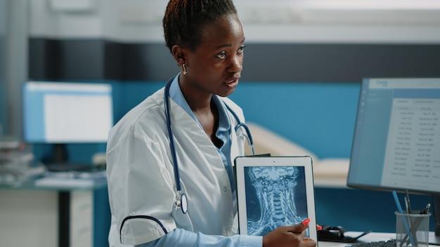 Nahaufnahme eines arztes, der mit radiographie auf das tablet-display zeigt