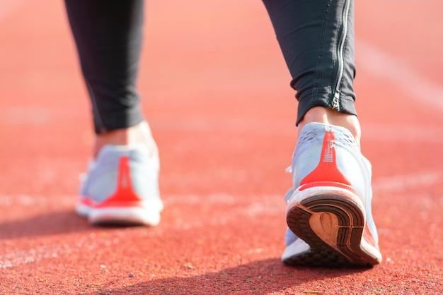 Nahaufnahme eines athleten immer bereit für das rennen auf einer laufstrecke. konzentrieren sie sich auf den schuh eines athleten, der kurz davor ist, ein rennen im stadion zu starten.