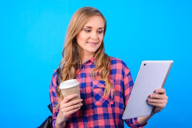 Nahaufnahme eines attraktiven, selbstbewussten, fröhlichen, aufgeregten, intelligenten, fröhlichen geschäftsfrau-freiberuflers, der teeladen genießt und videos auf dem pda-pad in der hand einzeln auf blauer oberfläche sieht