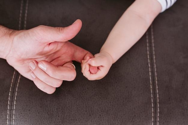 Nahaufnahme eines babys, das zu hause den finger des vaters hält. familien- und liebeskonzept