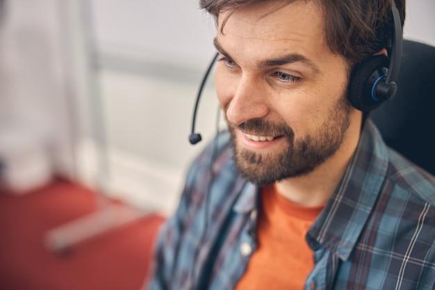 Nahaufnahme eines bärtigen jungen mannes im headset, der positive emotionen ausdrückt